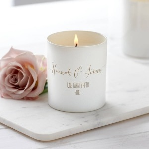 white personalised candle with bride and groom names